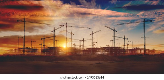 Cranes and building construction.Construction and real estate industry. Sunset and foundation structure of houses.
