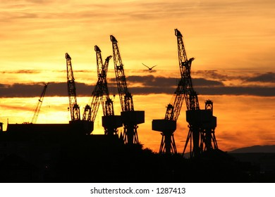 The cranes of a Clyde shipyard silhouetted by a Glasgow sunset