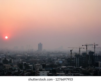 Cranes at construction site in golden sunshine evening with fog in winter in downtown of Bangkok, the capital of Thailand in southeast Asia.