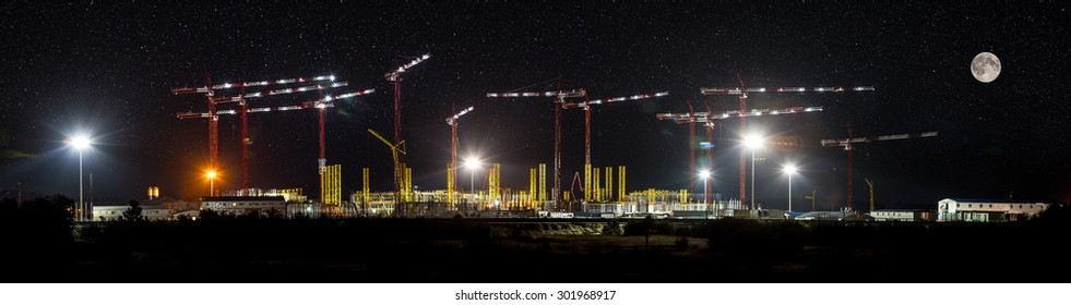Cranes at construction site, night panorama, stars