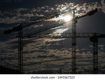 Cranes on a construction site with a cloudy sky during sundown