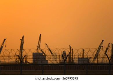 the cranes on working at construction side in evening time