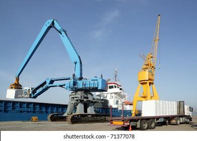 cranes in a port, unloading a ship