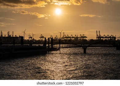 Cranes silhouetted against the evening sky in Hamburg Harbor, Germany, at dusk. The Port of Hamburg (Hamburger Hafen) is a sea port on the river Elbe. It is Germany's largest port.