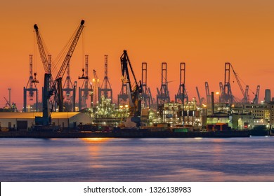 Cranes silhouetted against the evening sky in Hamburg Harbor, Germany, at dusk. The Port of Hamburg (Hamburger Hafen) is a sea port on the river Elbe. It is Germany's largest harbor.