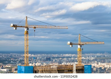 cranes at top of skyscraper under construction in Moscow city in autumn day