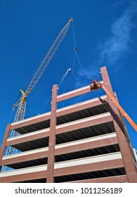 Cranes and workers erect a precast concrete office building. Teamwork and construction concept.