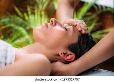 Craniosacral therapy massage. Therapist massaging woman's forehead.