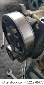 Crankshaft pulley. View on pulley on a car engine. Machine belt. Close up. Disassembled motor vehicle for repair. Parts in engine oil. Car engine repair.