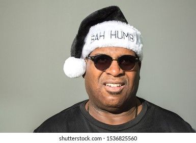 cranky middle aged African American man wearing sunglasses and a black and white Bah Humbug hat with pom pom against a solid background