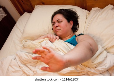 Cranky woman in bed holds out her hand to be left alone to sleep