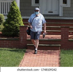 CRANSTON, RHODE ISLAND/USA- MAY 15, 2020: Masked United States Postal Service mail carrier, Richard Sowden, delivers mail in warm weather during the Coronavirus Pandemic