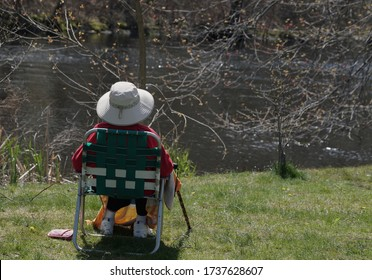 CRANSTON, RHODE ISLAND/USA- MAY 3, 2020: A woman sits by a river enjoying the sunshine and outdoors in Phase One Pandemic reopening.