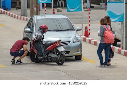 Crash of a motorcycle with a car, without serious damage. Driver are investigating the consequences of a crash on the street.