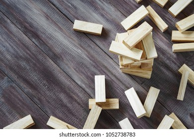 Crash of wooden building blocks tower on dark wood background with copy space. Collapse of wood blocks stack game background concept for business risk, imbalance, Collapse, destruction and Mistake