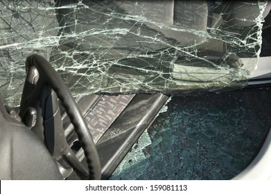 Crashed car on side with broken windows close-up