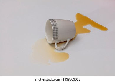 Crashed coffee cup. Black coffee has spread on a white table.