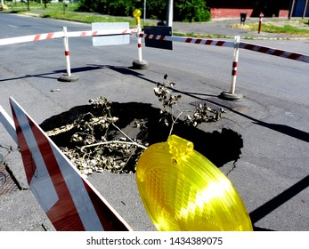crashed & collapsed asphalt road surface with big hole below. the result of erosion caused by storm water. road hazard. road maintenance. red & white wooden plank barrier on vinyl post & concrete base