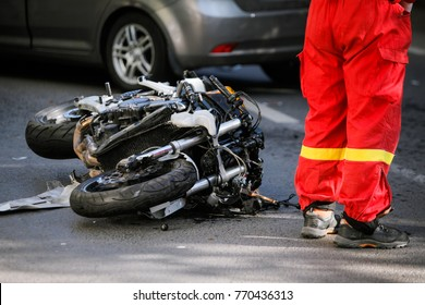 Crashed motorcycle after road accident with a car on a city street