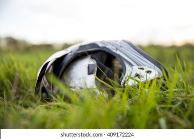Crashed motorcycle helmet lying on its side on long, uncut grass
