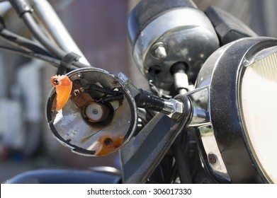 Crashed motorcycle turn indicator, closeup outdoor shot, concept of safety on the roads