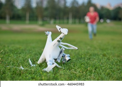 Crashed quadrocopter in park. Propeller damage. Operator running on the background