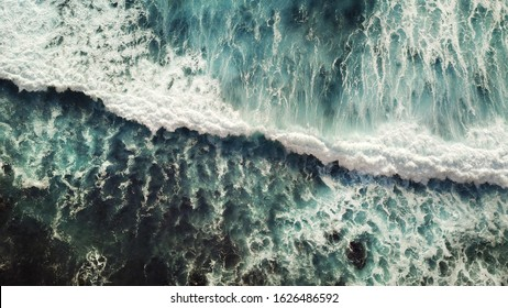 Crashing sea wave with plenty white foam and dynamic water view from above.