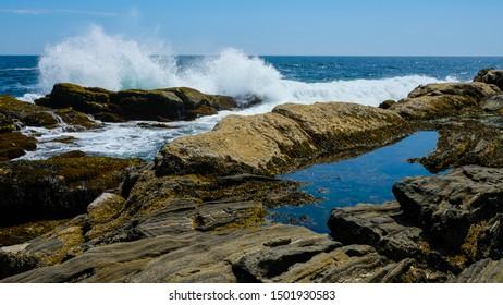 Crashing waves on rocky coastline in Maine, New England ocean
