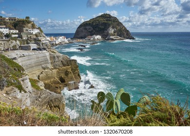 Crashing waves with a spikey cliff top island view to Sant'Angelo village on sea cliffs, with wild waves crashing against the rocks - Ischia, Italy