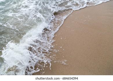 Crashing white waves on brown sand beach.