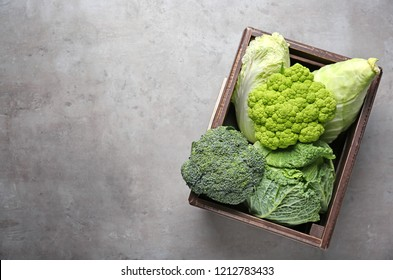 Crate with different kinds of cabbage on grey table