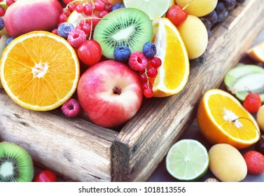 Crate of fresh ripe sweet fruits: apple, orange, grapefruit, qiwi, banana, lime, blueberry, strawberry, raspberry, peach, cherry; selective focus