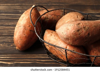 crate with  fresh ripe sweet potatoes on a wooden table, top view