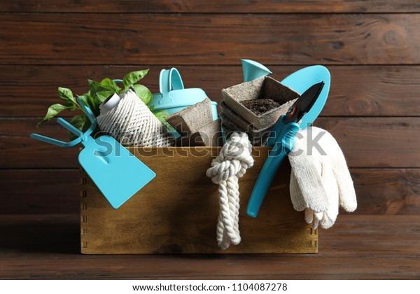 Crate with professional gardening tools on wooden table