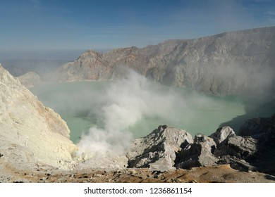 Crater with acidic crater lake, Kawah Ijen the famous tourist attraction, where sulfur is mined. Extraction of sulfur in the crater of a volcano. Sulfur gas, smoke.