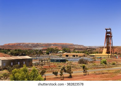 crater of huge open pit gold mine in Kalgoorlie Boulder of Western Australia with surrounding industrial zone, warehouses and supplies