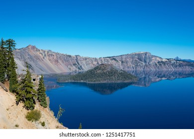 Crater Lake National Park offers beautiful views of the lake with amazing blue water and a few islands in the top of a volcano caldera.