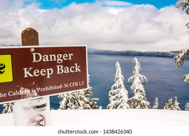 "Crater Lake, OR/USA - May 17 2019: ""Danger Keep Back"" sign warns visitors of snowy slopes that drop into  Lake. The view by the sign is stunning with the bright blue lake, Wizard Island & blue sky."