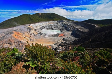 The crater and the lake of the Poas volcano in Costa Rica. Volcano landscape from Costa Rica, with blue sky with clouds.