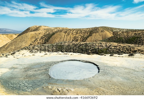 Crater of mud volcano. Clay mountains in the background