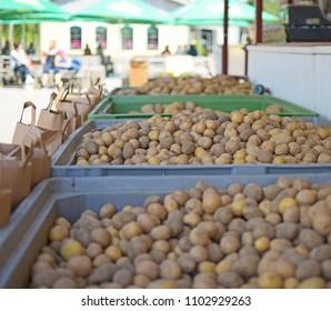Crates full of raw loose potatoes (Solanum Tuberosum) at a market stall