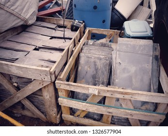Crates of purple roofing slates at a salvage yard in the UK.