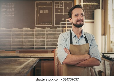 Cratsman looking away in a thoughtful manner with his arms folded while standing in his carpentry workshop and smiling to himself