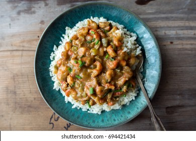 Crawfish etouffee over rice on a turquoise blue plate.