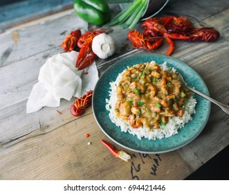 Crawfish etouffee over rice on a turquoise blue plate. Shown with scallions, green pepper, garlic and raw whole crawfish or crayfish.