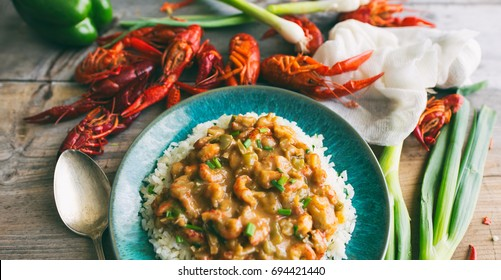 Crawfish étouffée over rice on a turquoise blue plate.