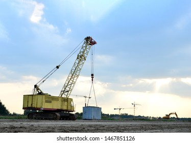 Crawler crane on the construction site for loading and unloading and construction works. Heavy industrial machinery on the background of a sunset
