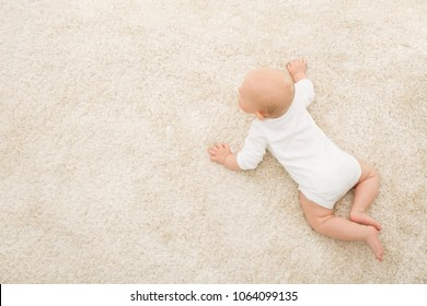 Crawling Baby on Carpet Background, Infant Kid Top View, Newborn Child Lying on Beige Blanket