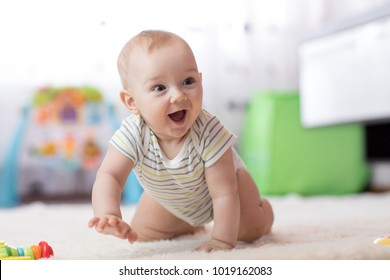 crawling funny baby boy in nursery at home