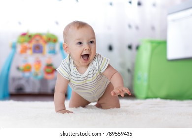 crawling funny baby boy in nursery at home.